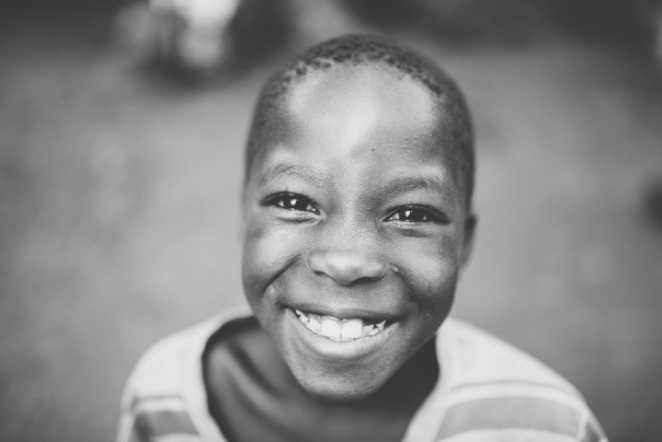 black and white photo of child smiling at camera
