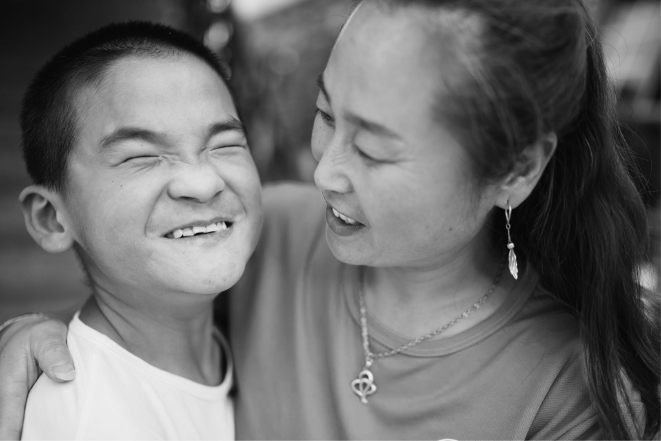 black and white photo of Asian boy and woman smiling at each other