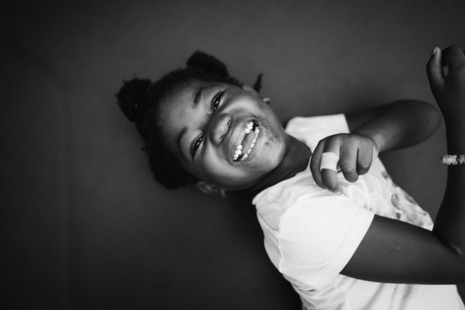 black and white photo of little girl laying down laughing